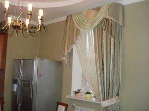 Окно кухни оформлено шторами